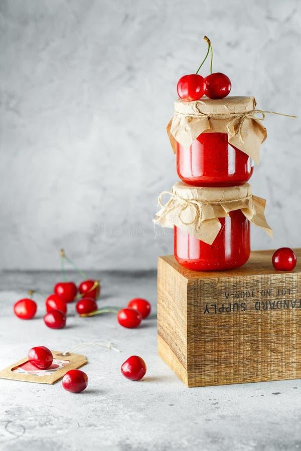 Atasco de cereza hecho en casa en el tarro de cristal en la caja de madera en el fondo gris Dos tarros de atasco de cereza en la  imagen de archivo libre de regalías