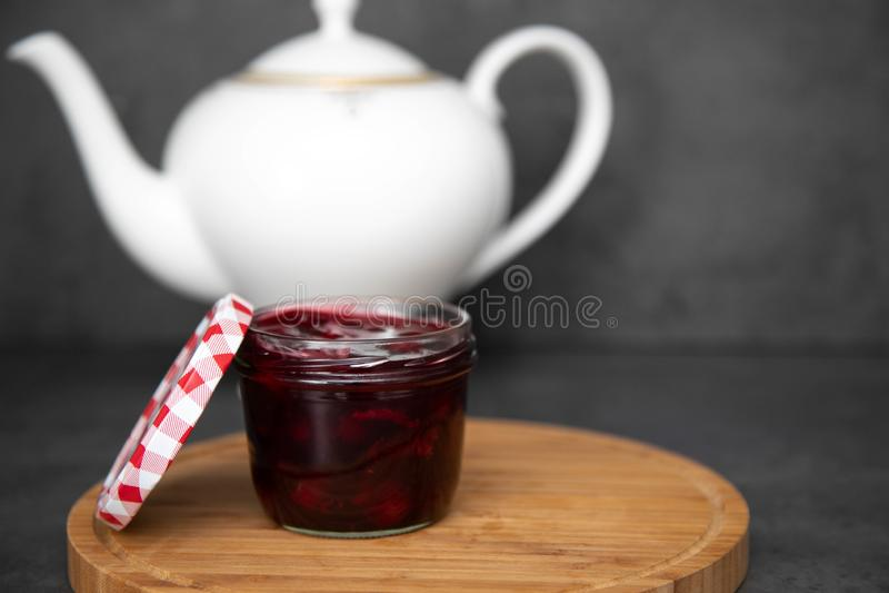 Atasco de cereza, atasco, jalea en un tarro de cristal con una tapa roja y blanca al lado de un tablero redondo de madera, tabler imágenes de archivo libres de regalías