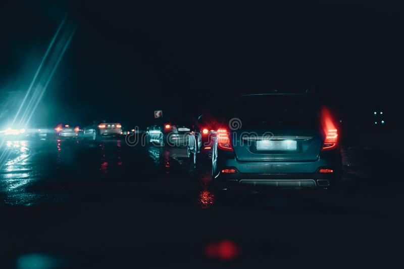 Atasco de la noche en tiempo lluvioso de la cama peligro del camino durante huracán luces rojas y azules de la cola de coches imagen de archivo libre de regalías