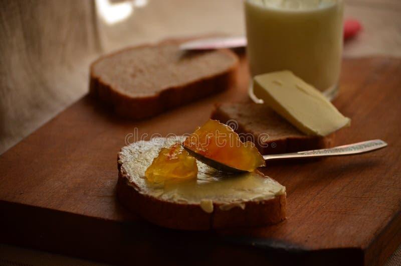 Atasco del pan oscuro, de la leche, de la mantequilla y del albaricoque imagenes de archivo
