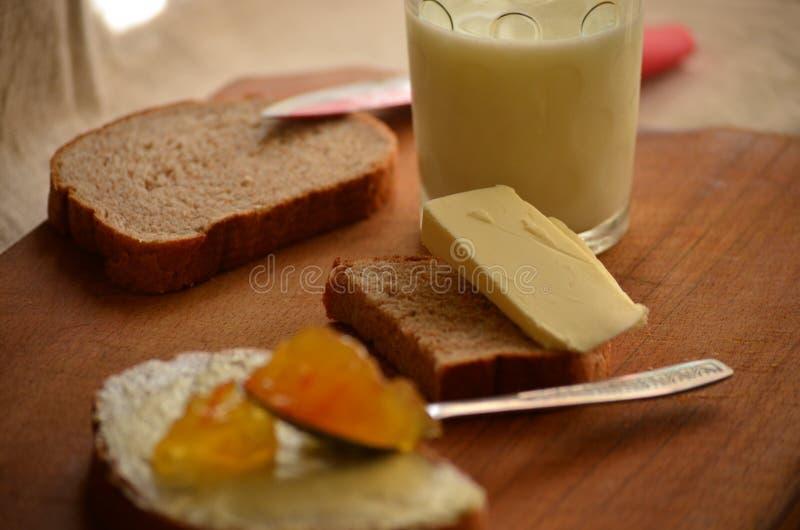 Atasco del pan oscuro, de la leche, de la mantequilla y del albaricoque fotos de archivo