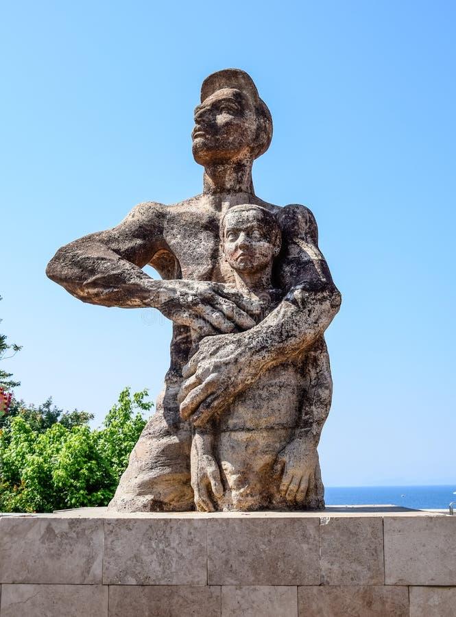 Ataturk är ett beskyddande av barn, monument till ataturken, som skyddar pojken arkivbilder
