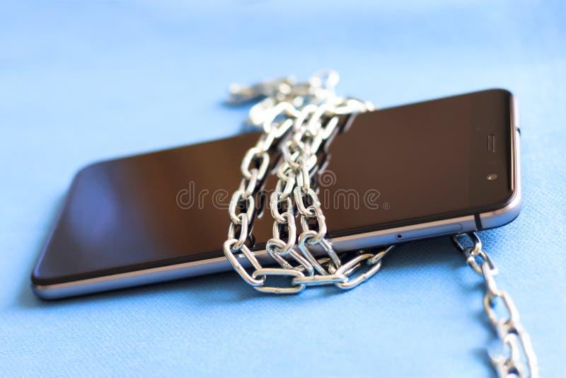 Ate el teléfono con una cadena del metal Fondo gris claro no fotografía de archivo libre de regalías