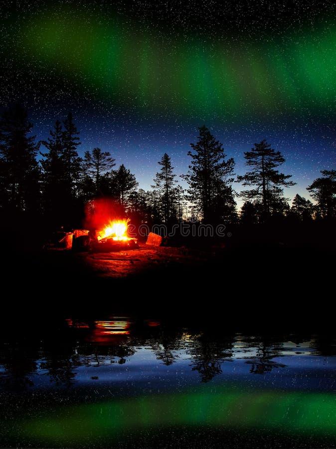 Ateie fogo ao burning na noite em uma floresta com aurora boreal imagens de stock