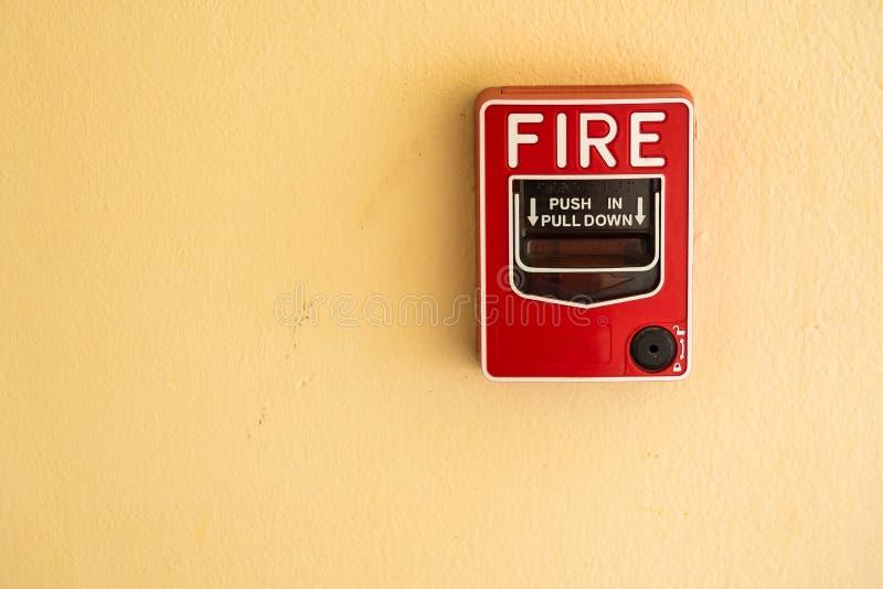 Ateie fogo ao interruptor de vidro do alarme da ruptura na parede do cimento foto de stock