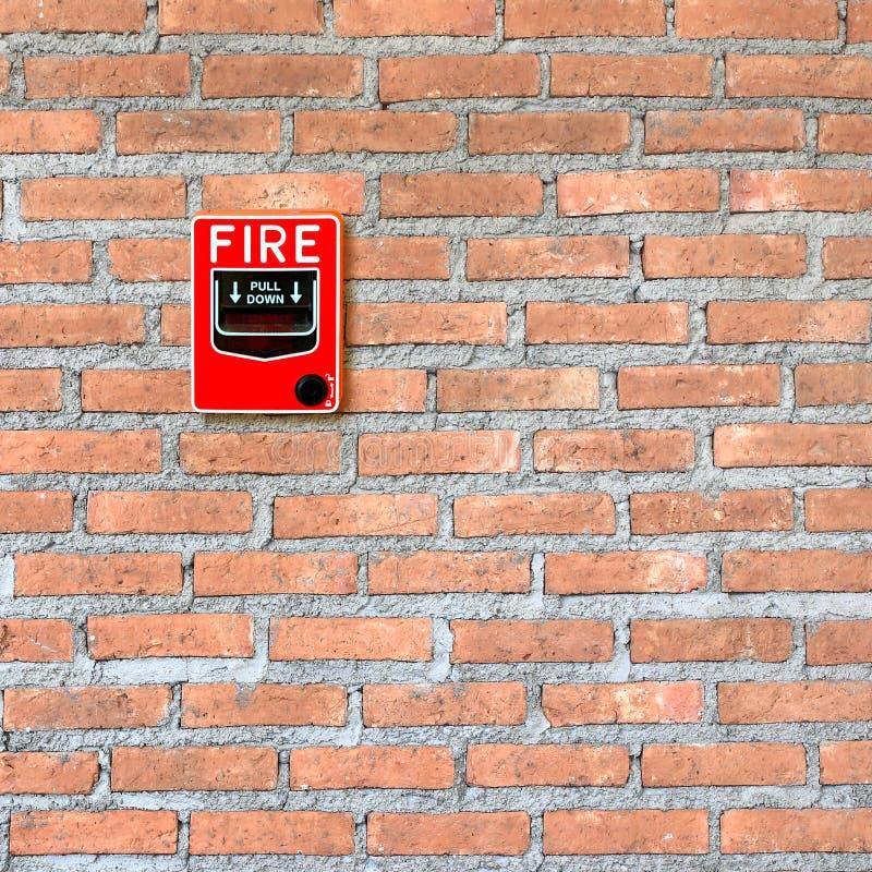 Ateie fogo ao interruptor de vidro do alarme da ruptura no fundo da parede de tijolo imagem de stock