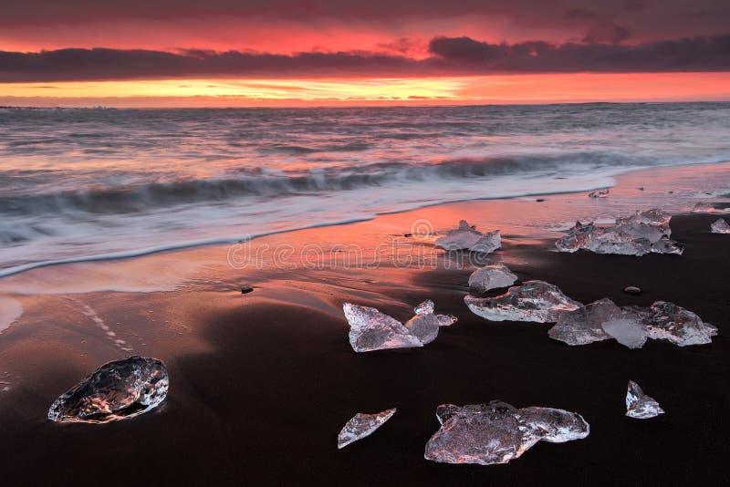 Ateie fogo ao nascer do sol do jokulsarlon na praia em Islândia foto de stock royalty free