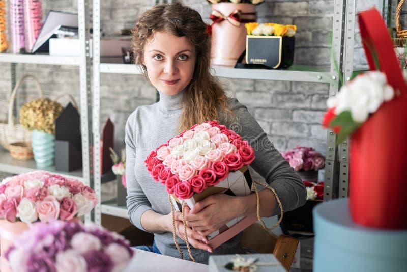 Atelier de fleur : une fille de fleuriste tient un beau grand bouquet des roses de rose et blanches images stock