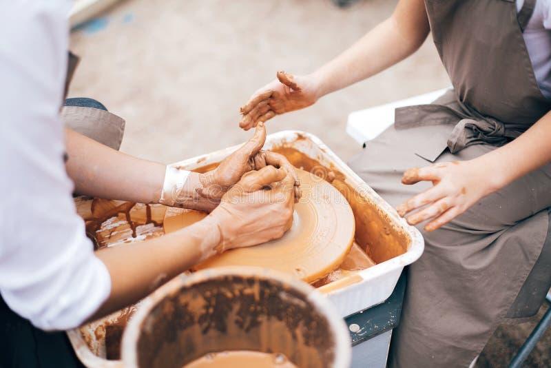 Atelier de poterie Mains de l'adulte et de l'enfant faisant la poterie, fonctionnant avec le plan rapproché humide d'argile Proce photographie stock libre de droits