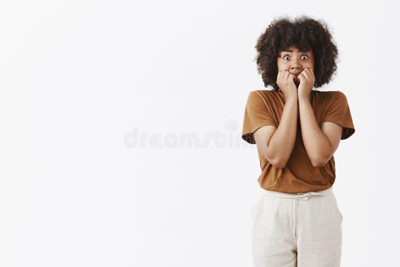 Atelieraufnahme der erschrockenen Afroamerikanerjugendlichen in knallenden Augen der Benommenheit an der Kamera und am Abdeckungs lizenzfreies stockfoto