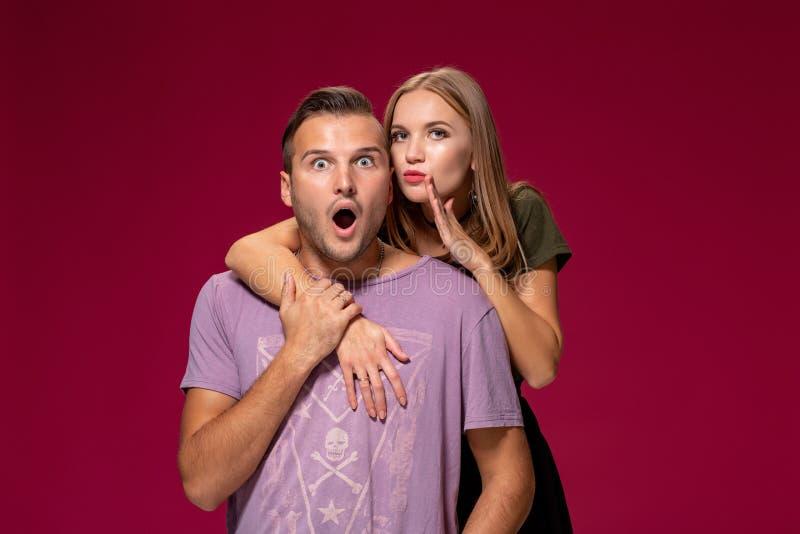 Atelieraufnahme der geheimen jungen Frau und Mann halten Zeigefinger auf Lippen, stehen neben einander, sagen privaten Informatio lizenzfreie stockfotografie