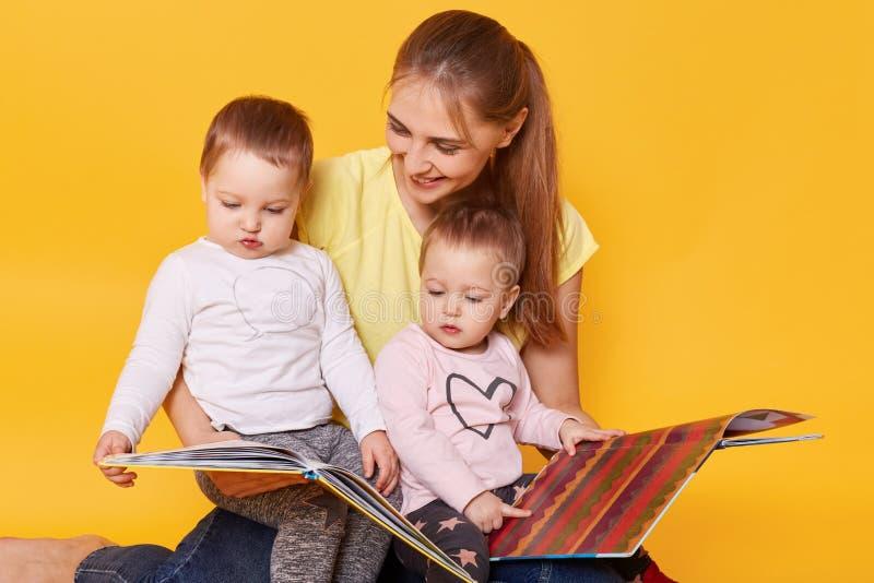 Atelieraufnahme der glücklichen Familie: Mutter und kleine Zwillingsmädchen, die auf Boden, Lesebüchern und ansehenden hellen int lizenzfreies stockbild