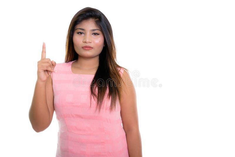 Atelieraufnahme der jungen fetten persischen Jugendlichen, die oben Finger zeigt stockbild