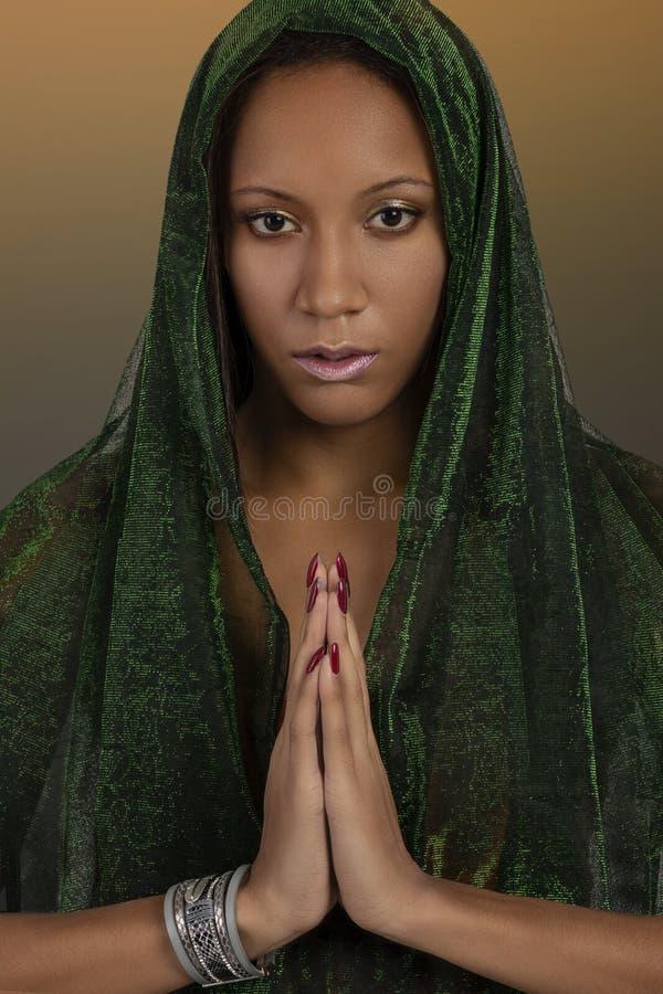 Atelieraufnahme der jungen Frau des mulatta mit einem grünen Schal auf dem praing Kopf stockbild