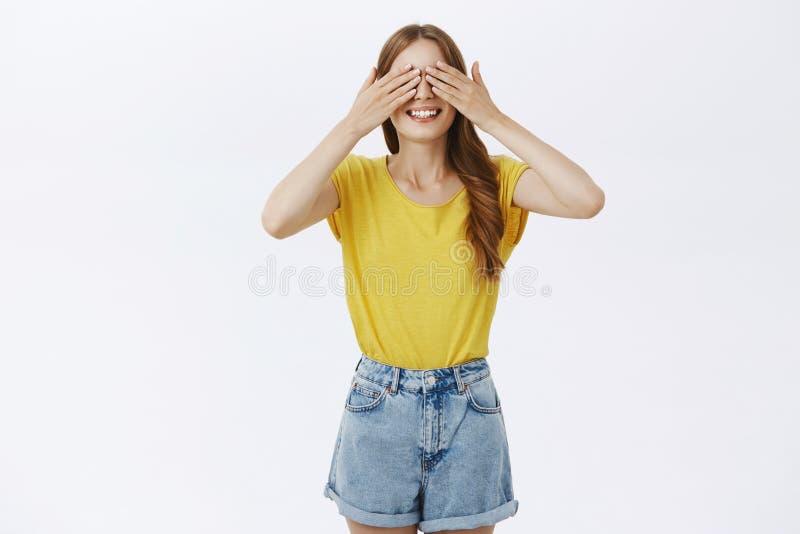 Atelieraufnahme der netten charismatischen Frauenstellung mit Erwartung über schließenden Augen des grauen Hintergrundes und an h lizenzfreies stockbild
