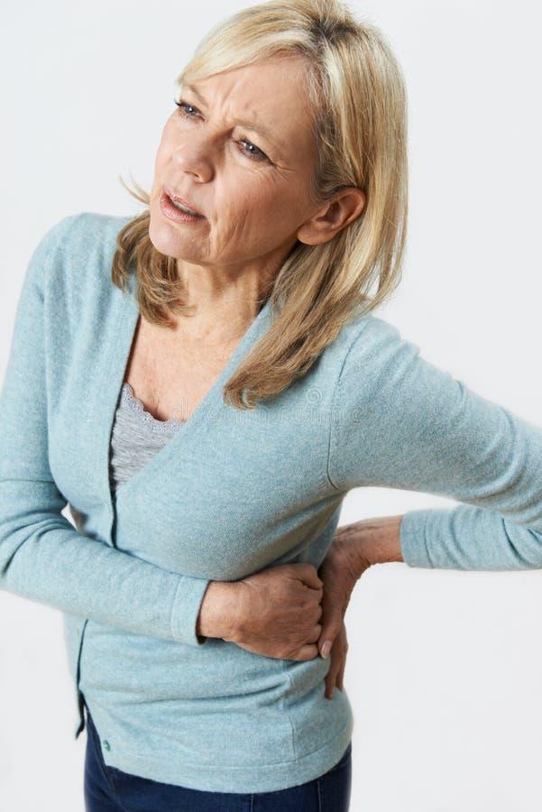 Atelieraufnahme der reifen Frau leiden mit den Nieren-Schmerz lizenzfreies stockfoto