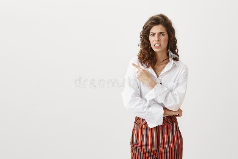 Atelieraufnahme der reizend schlanken Frau in der modischen Kleidung nach links zeigend mit dem Zeigefinger beim Sein zweifelhaft stockbild