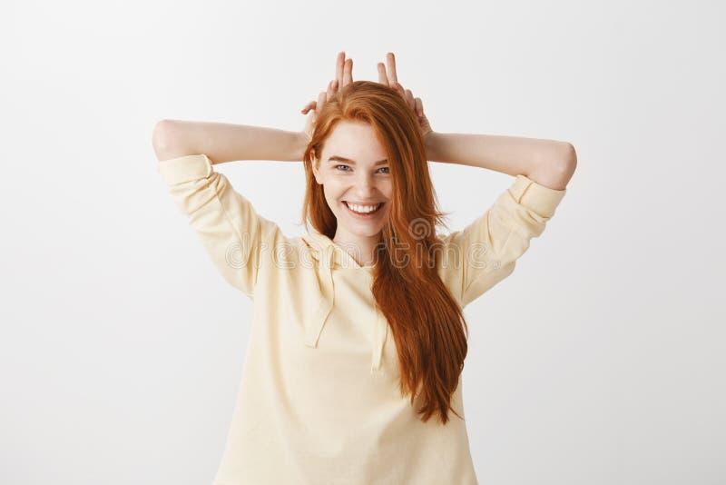 Atelieraufnahme der schönen frechen Freundin mit dem roten Haar, das Finger hinter Kopf als ob Ohren oder Teufelhörner hält lizenzfreies stockfoto