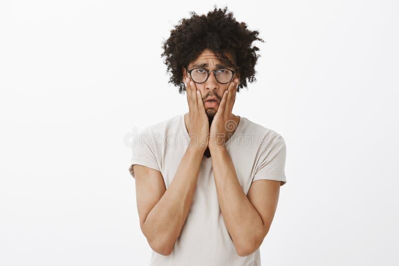 Atelieraufnahme des düsteren erschöpften und gebohrten netten Kerls mit Afrohaarschnitt in den Gläsern, Backen mit Palmen zusamme stockbilder