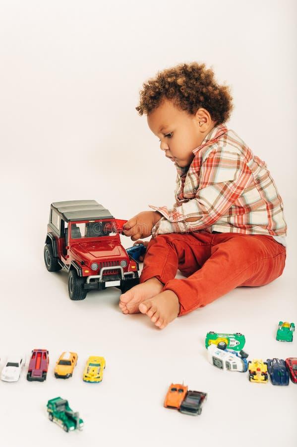 Atelieraufnahme des entzückenden afrikanischen einjährigen Babys, das mit bunten Autos spielt stockbild