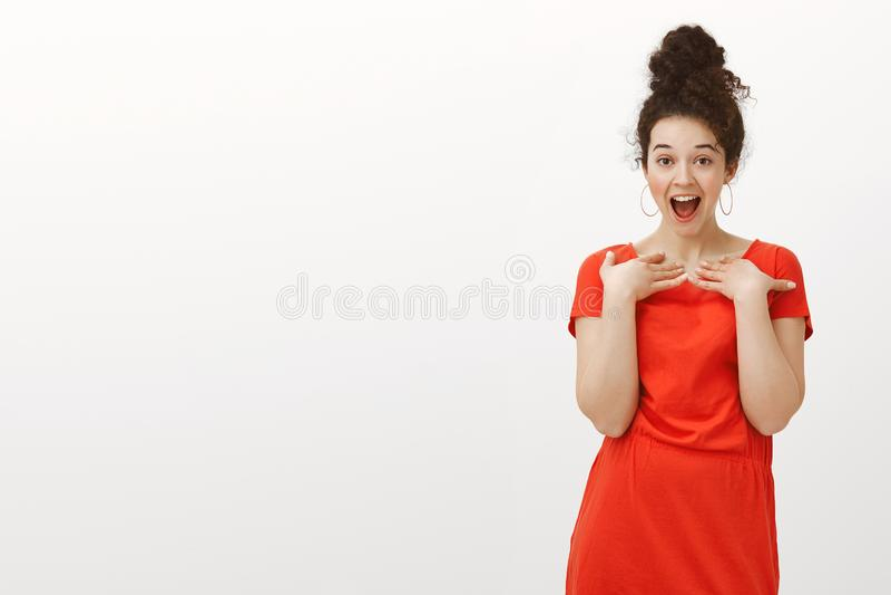 Atelieraufnahme des erfreuten beeindruckten reizend Mädchens mit dem gelockten Haar in der Brötchenfrisur, keuchend, fallender Ki lizenzfreie stockfotografie