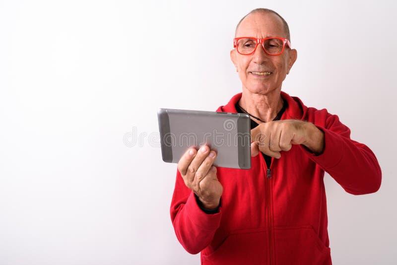 Atelieraufnahme des glücklichen kahlen älteren Mannes, der digitales t lächelt und verwendet stockfotografie