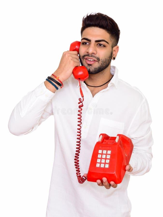 Atelieraufnahme des jungen glücklichen indischen Mannes, der auf Telefon isola spricht stockfotografie