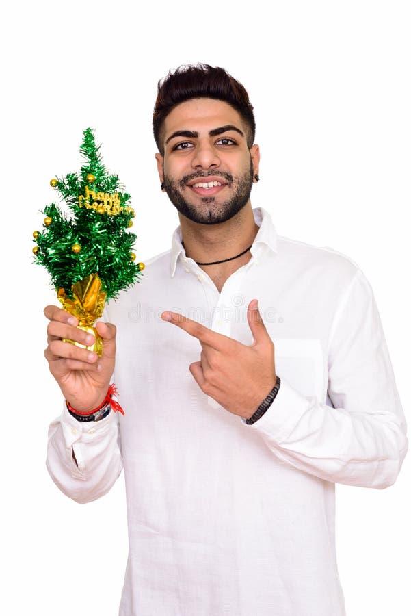 Atelieraufnahme des jungen glücklichen indischen Mannes, der guten Rutsch ins Neue Jahr tre hält stockbilder