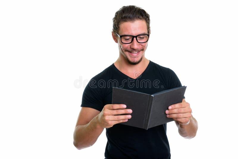 Atelieraufnahme des jungen glücklichen lächelnden Mannes während Lesebuch mit e stockbild
