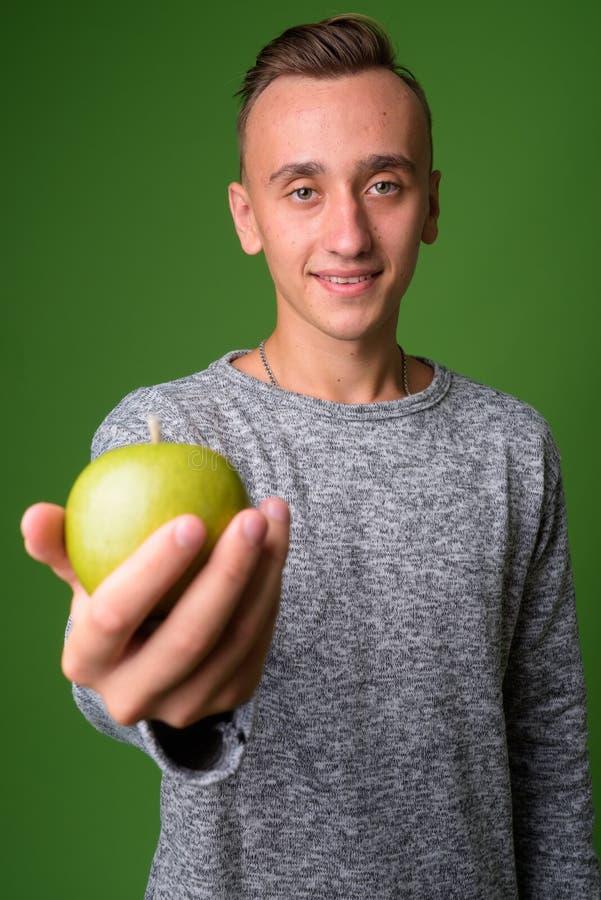Atelieraufnahme des jungen gut aussehenden Mannes gegen grünen Hintergrund stockfotografie
