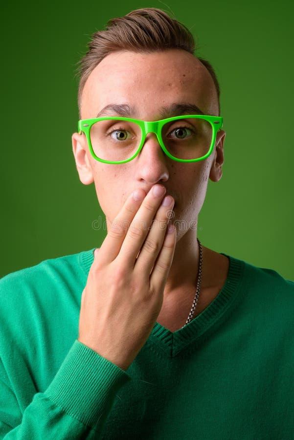 Atelieraufnahme des jungen gut aussehenden Mannes gegen grünen Hintergrund lizenzfreie stockfotos