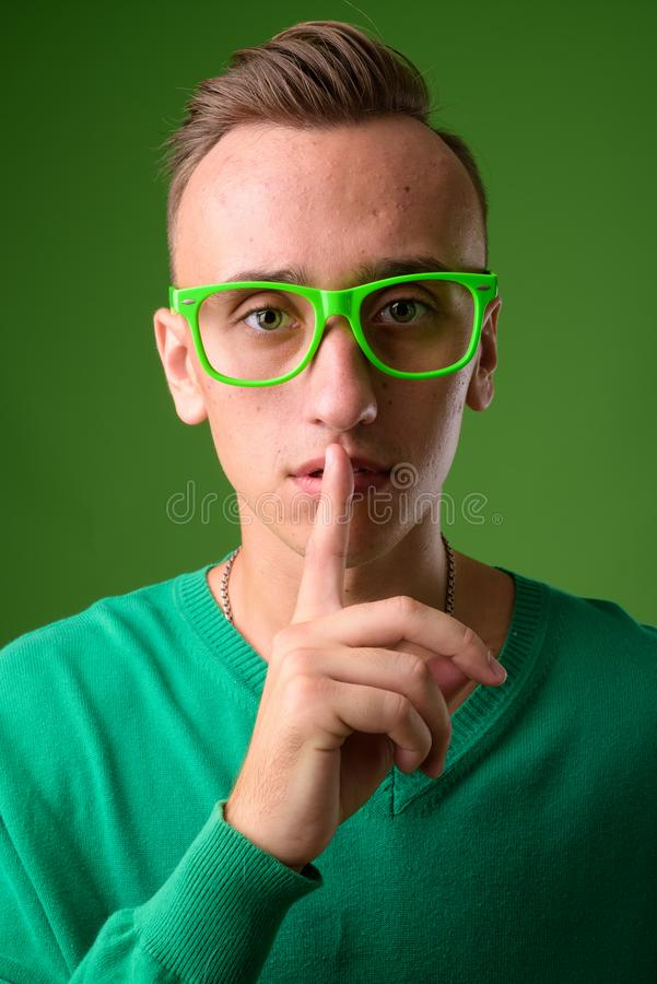 Atelieraufnahme des jungen gut aussehenden Mannes gegen grünen Hintergrund lizenzfreies stockfoto