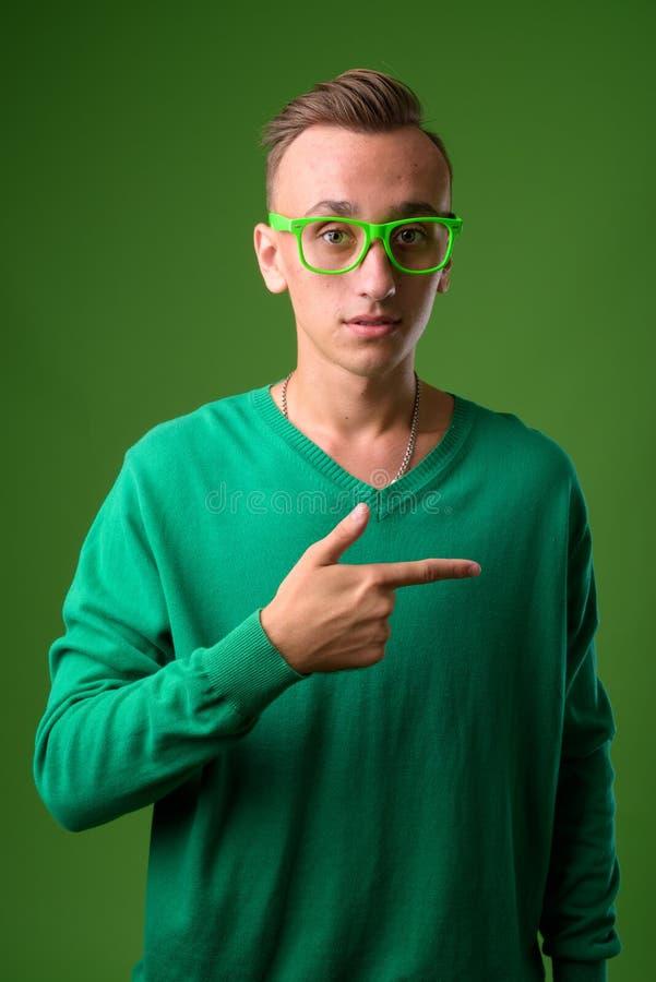 Atelieraufnahme des jungen gut aussehenden Mannes gegen grünen Hintergrund stockfotos