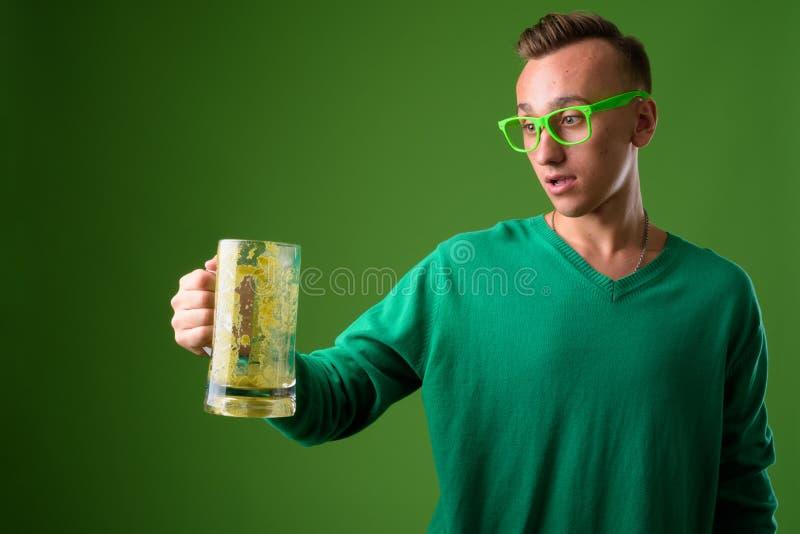 Atelieraufnahme des jungen gut aussehenden Mannes gegen grünen Hintergrund lizenzfreies stockbild