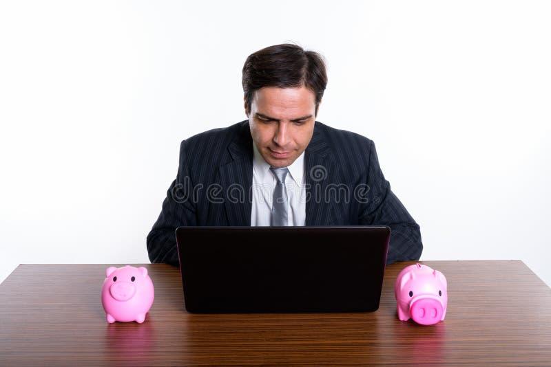 Atelieraufnahme des jungen persischen Geschäftsmannes, der Laptop mit zwei p verwendet stockfoto