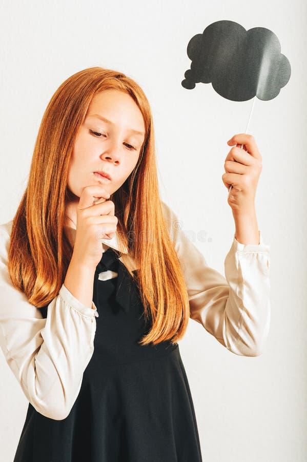Atelieraufnahme des jungen rothaarigen Kindermädchens, das denkende Blase des Papiers hält lizenzfreie stockbilder