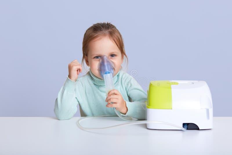 Atelieraufnahme des kleinen Mädchens Inhalator, tragende zufällige blaue Strickjacke nehmend, sitzend am weißen Schreibtisch, Auf stockfotos