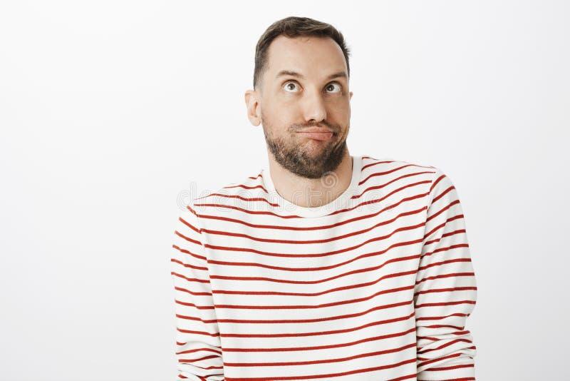Atelieraufnahme des lustigen kindischen bärtigen Mannes in gestreiftem Pullover, die Gesichter oder Nachäffen machend und oben sc lizenzfreie stockfotos