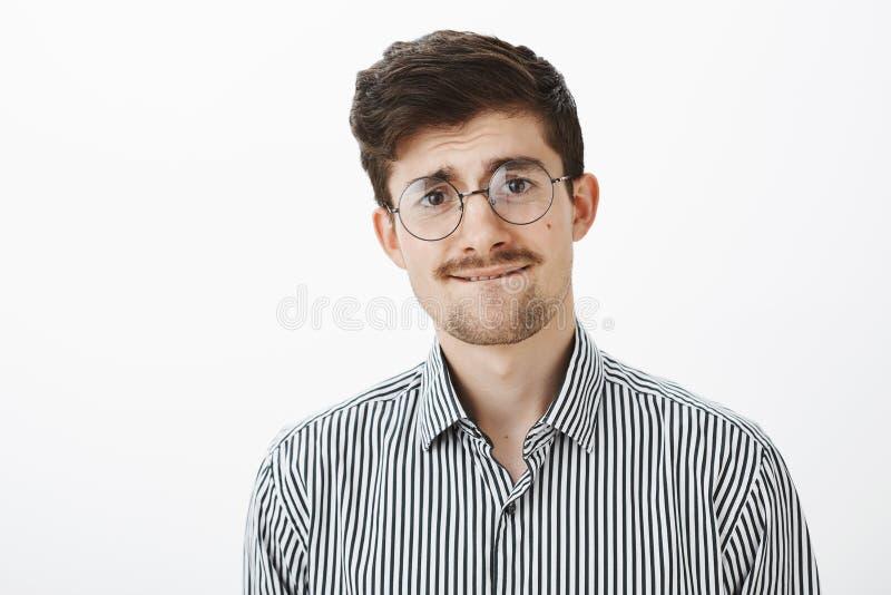 Atelieraufnahme des nervösen ungewissen lustigen bärtigen Kerls, in den runden Gläsern, in beißender Lippe und etwas in die Stirn stockbild