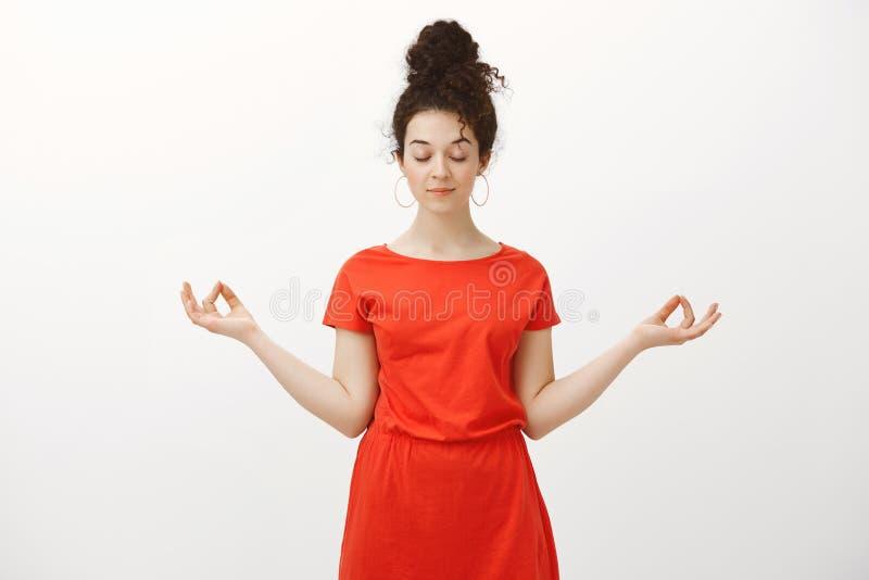 Atelieraufnahme des ruhigen entspannten weiblichen Mädchens mit dem gelockten Haar gekämmt in der Brötchenfrisur, ausgebreitete H lizenzfreies stockfoto