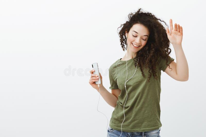 Atelieraufnahme des stilvollen sorglosen europäischen Mädchens mit dem gelockten Haar, tanzend mit den angehobenen Händen und bre stockfotografie