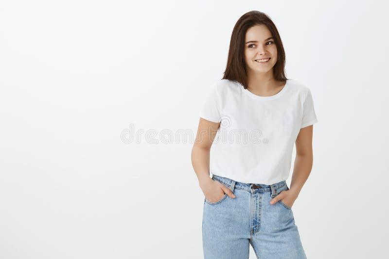 Atelieraufnahme des stilvollen weiblichen städtischen Mädchens mit dem dunklen Haar in den modischen Jeans und im T-Shirt, Händch stockfoto