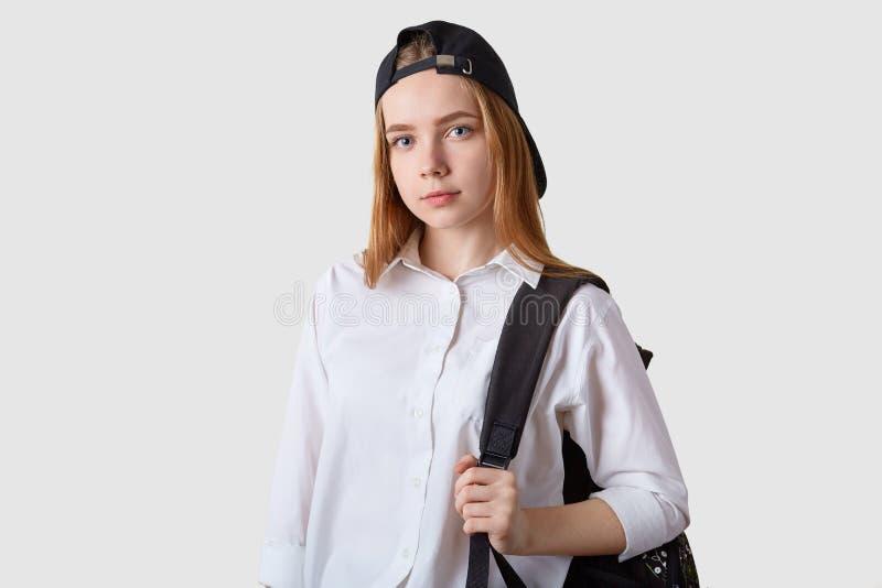 Atelieraufnahme des Studentenmädchens lokalisiert über der tragenden Bluse und Rucksack des weißen Hintergrundes, betrachtend ges lizenzfreie stockfotos