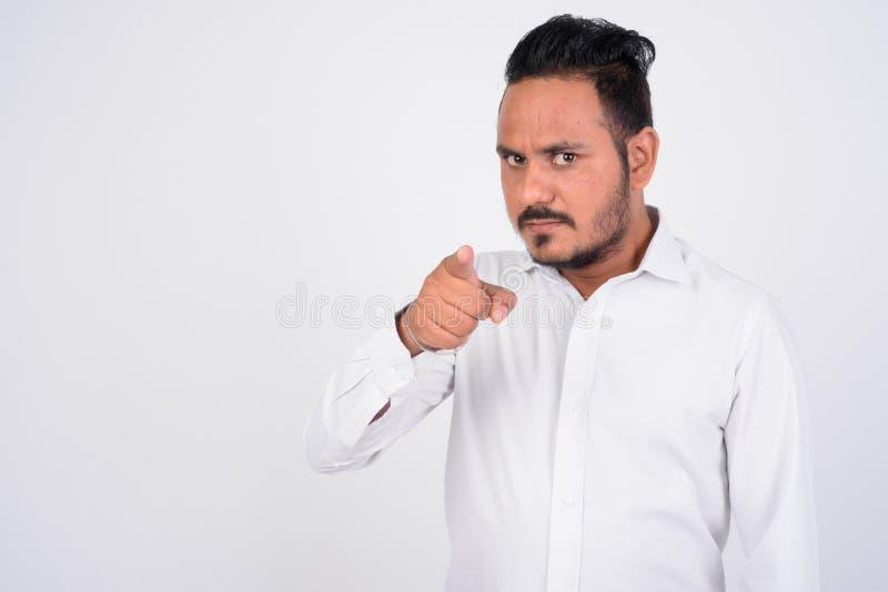 Atelieraufnahme des verärgerten bärtigen indischen Geschäftsmannes, der auf Kamera zeigt lizenzfreie stockfotos