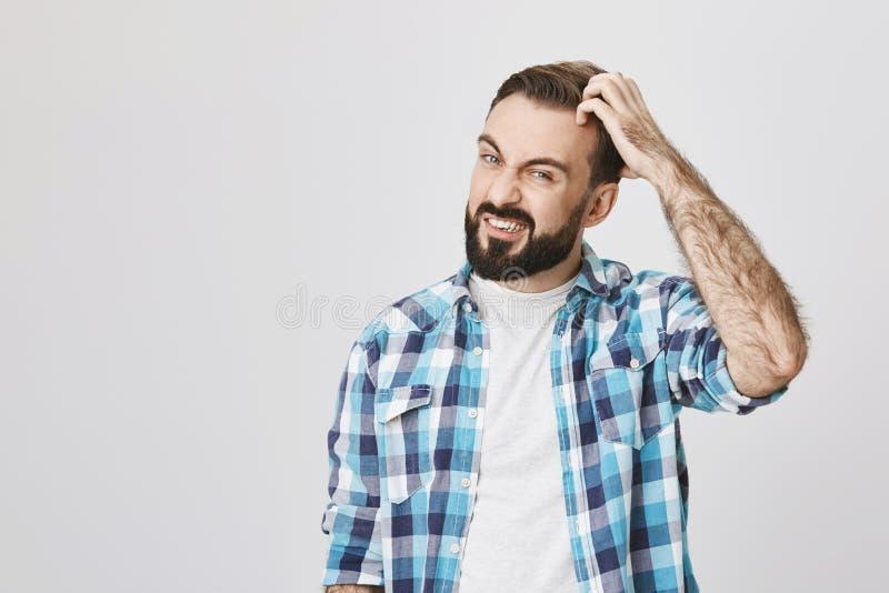 Atelieraufnahme des wütenden bärtigen Mannes, der ungefähr seinen Kopf scretching und Verwirrung, über grauem Hintergrund ausgedr lizenzfreies stockfoto