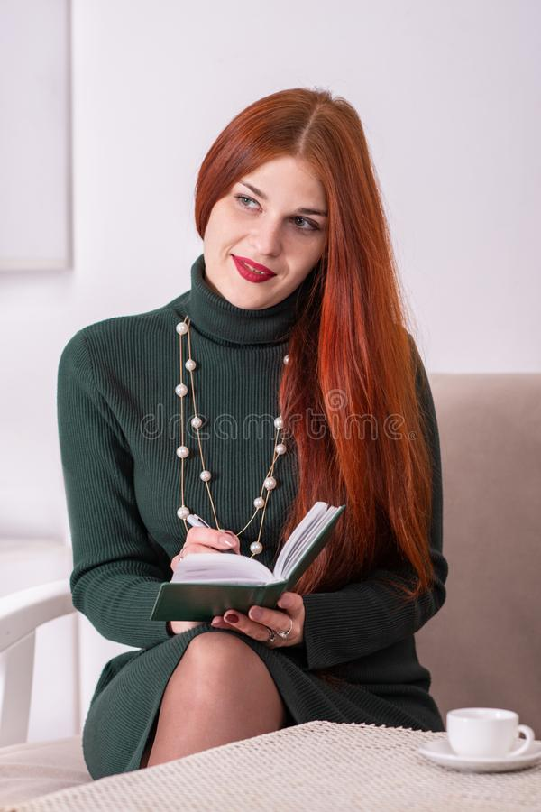 Atelieraufnahme einer jungen Frau, die grünes Kleid mit dem langen roten Haar trägt Sie sitzt an einem Tisch mit einer Notizbuch- stockfotos