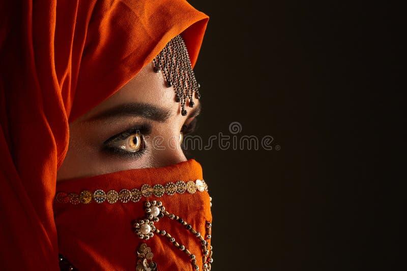 Atelieraufnahme einer jungen h?bschen Frau, die das Terrakotta hijab verziert mit Pailletten und Schmuck tr?gt Arabische Art stockfoto