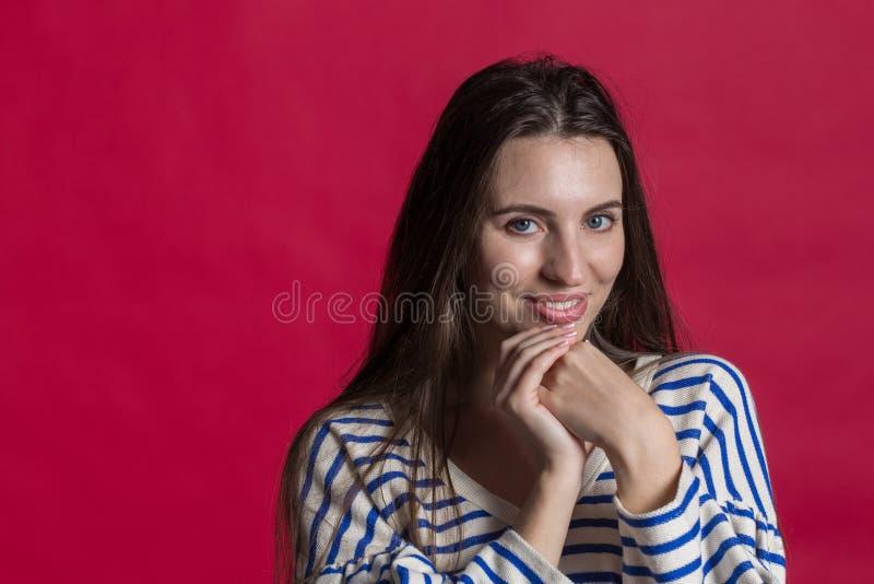 Atelieraufnahme einer reizenden Schönheit lokalisiert gegen eine leere rote Studiowand lizenzfreie stockfotos
