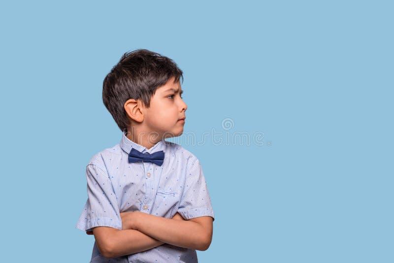 Atelieraufnahme eines ernsten Jungen, der blaues Hemd mit Bogen gegen blauen Hintergrund mit Kopienraum trägt stockbild