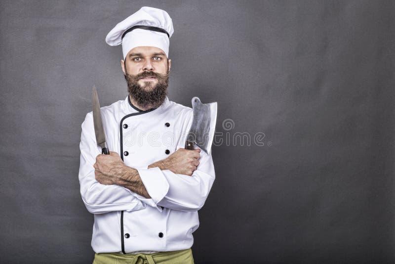 Atelieraufnahme eines glücklichen bärtigen jungen Chefs, der scharfe Messer hält stockbild